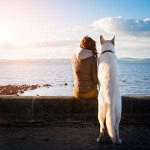 Woman and dog by water - essential oils for dogs